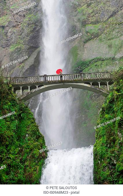 Woman with red umbrella on footbridge over Multnomah Falls, Columbia River Gorge, USA