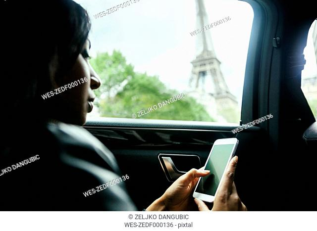 France, Paris, young woman sitting in a car looking at her smartphone