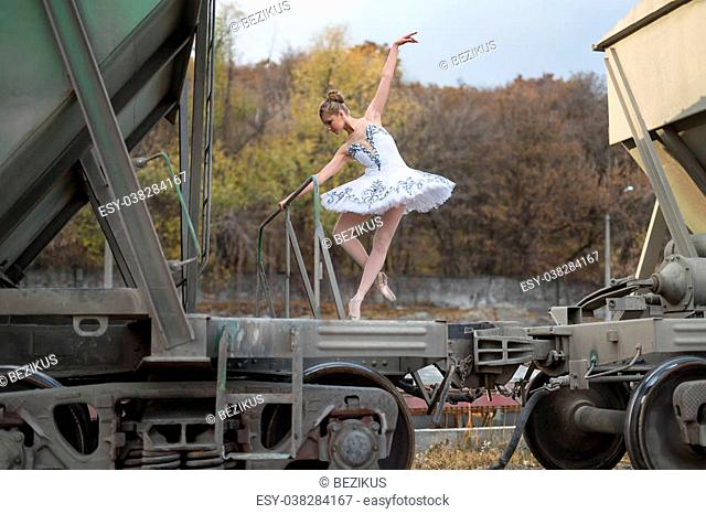 Nice young ballerina making a pose while standing on a freight wagon. She is wearing a white tutu with ballet shoes. There are many trees behind her