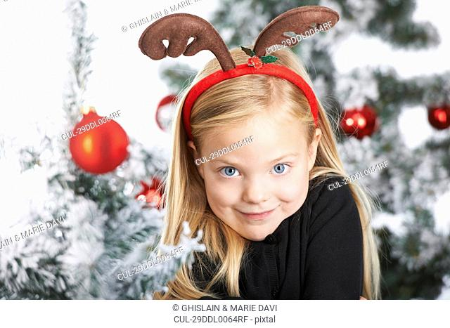 Girl with a deer-headband by the tree