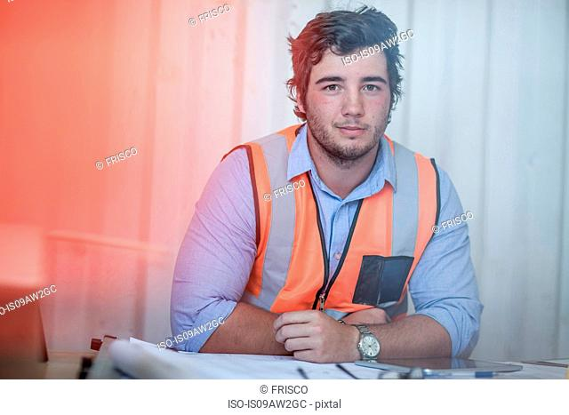 Portrait of young male construction worker sitting at desk in portable cabin