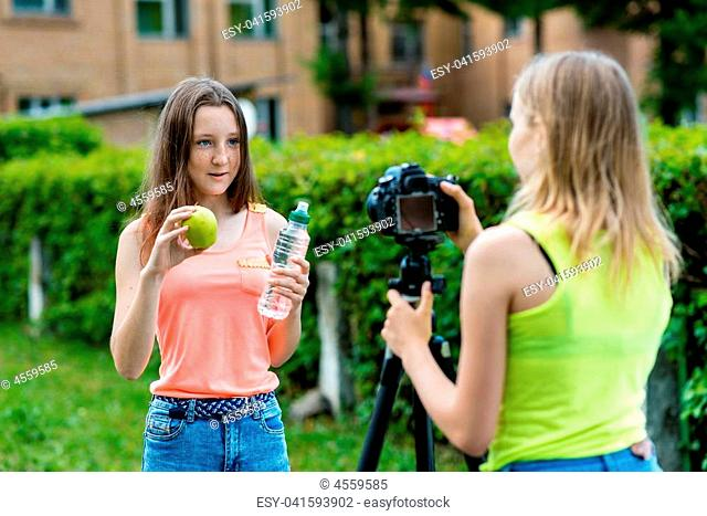 For girl schoolgirls, summer in nature. Records a video about healthy eating. In his hands holds a green apple and a bottle of water