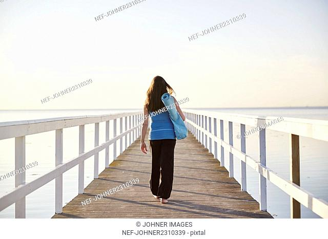 Woman walking on pier at seaside