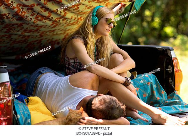 Young woman wearing headphones with boyfriend in pick up boot whilst camping
