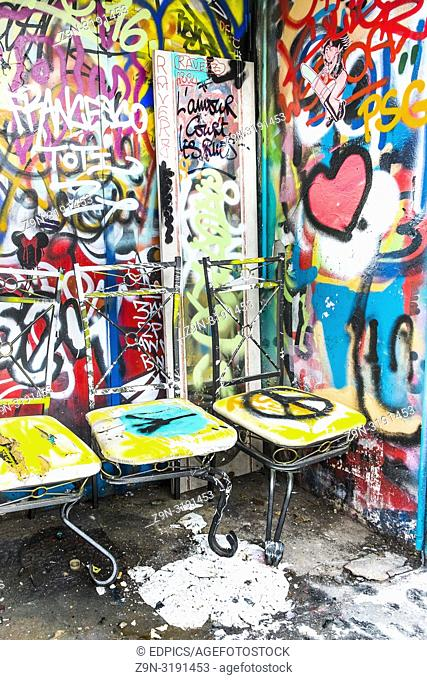 painted chairs in front of grafitti covered wall, paris, ile de france, france
