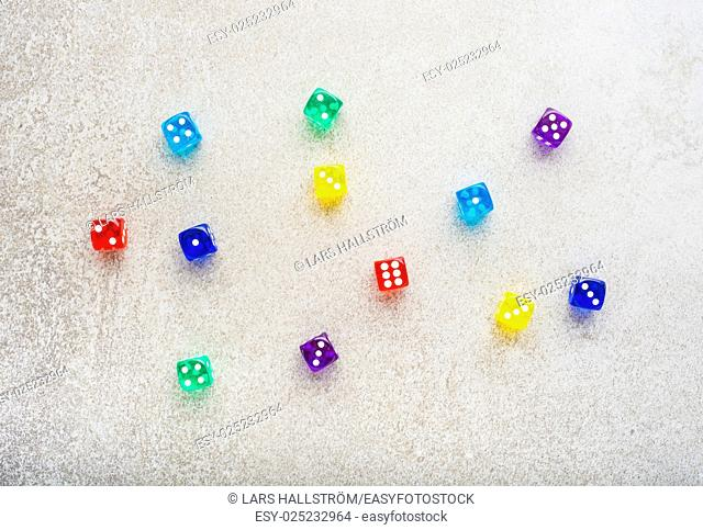 Dice in a variety of colors on stone table, symbol of chance and luck. Concept of diversity, leisure game or numbers
