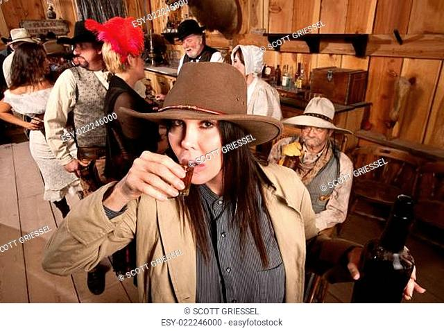 Cowgirl Sips Whiskey in Tavern