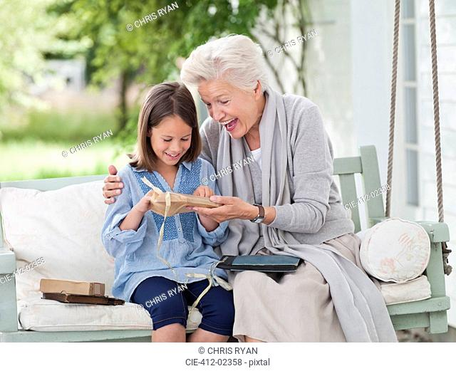 Woman giving granddaughter present in porch swing