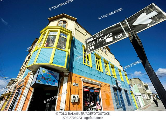 Chile, Patagonia, Punta Arenas (Sandy Point), Road sign in front of old colorful building and store