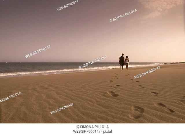 Spain, Tenerife, back view of young couple in love walking on sandy beach
