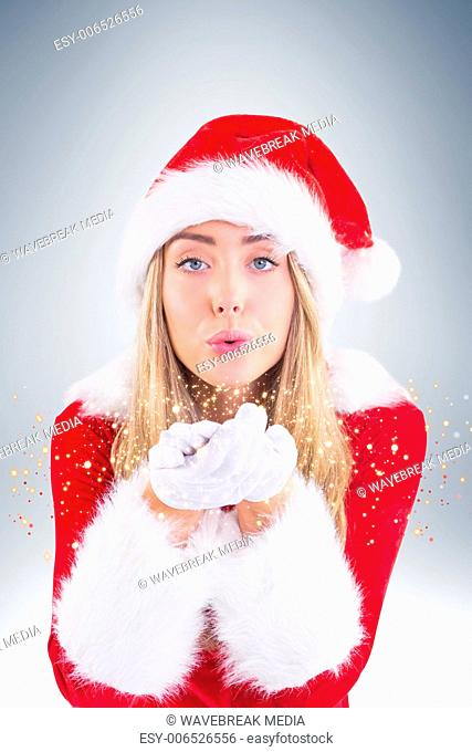 Pretty santa girl blowing over hands