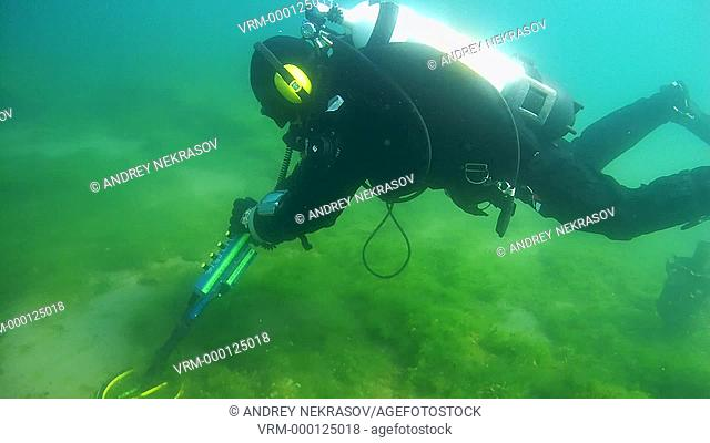 Diver with the metal detector searching for underwater treasure , lake Baikal, Siberia, Russia, Eurasia