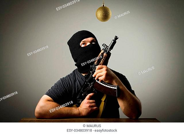 Man in mask with gun and Christmas ball which is above his head. Waiting of Christmas and New Year