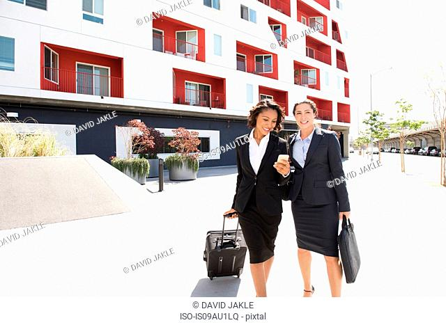 Two businesswomen walking outdoors, pulling suitcase