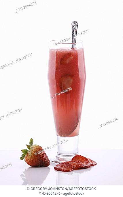 A strawberry drink with real strawberries in a studio background