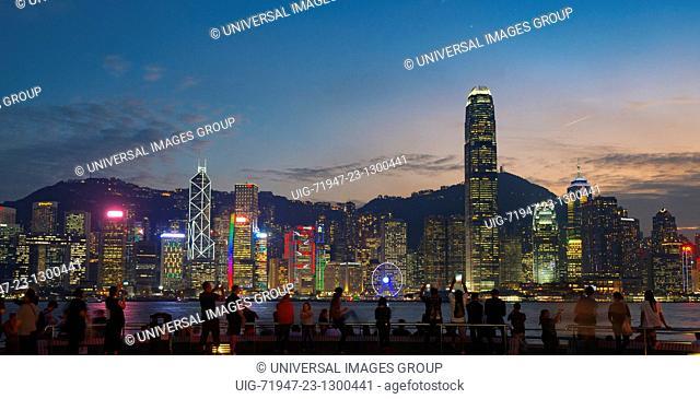 Tsim Sha Tsui promenade, and tourists enjoying the evening view of Hong Kong Island, Hong Kong, China