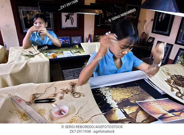 Women Embroiderer paints for souvenirs for the toruists in a studio, Hanoi, Vietnam