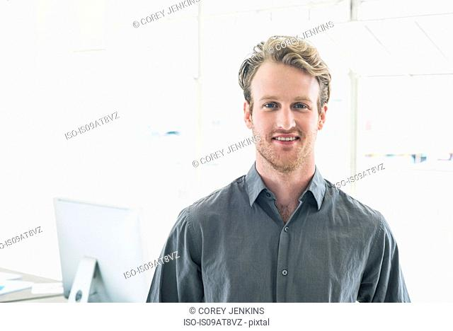 Smiling businessman by office window