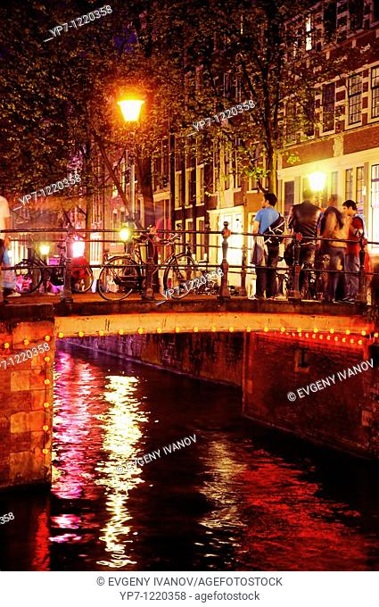 Neon reflections in canal in red light district, Amsterdam  People and bike on the bridge