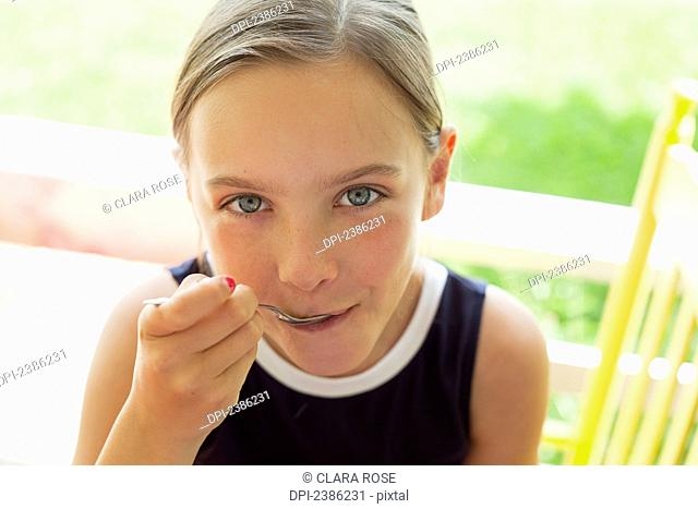 Young girl eating with a spoon outside in summer; Charlevoix, Quebec, Canada