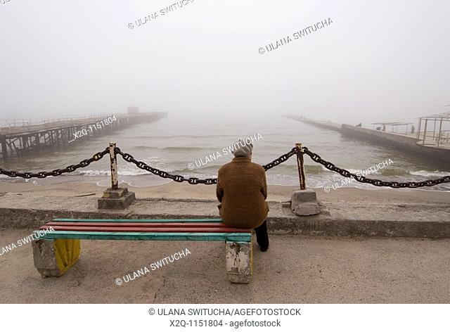 A lone woman looks at the Black Sea in Odessa Ukraine