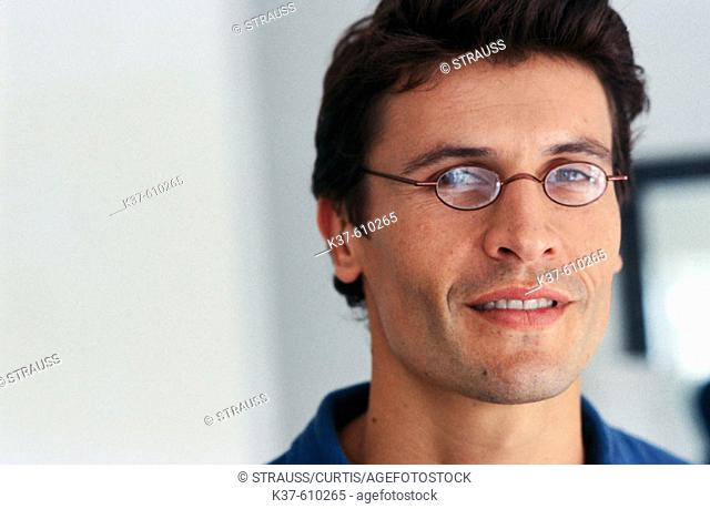 Young man wearing reading glasses