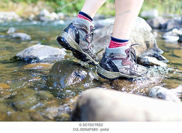 Hiker's feet walking on stones in shallow stream
