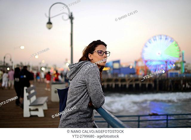 Attractive young woman relaxing in Santa Monica pier, California
