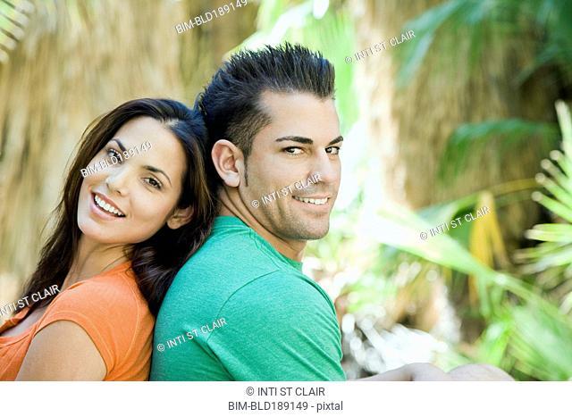 Hispanic couple relaxing in tropical area