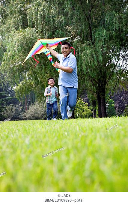 Chinese father and son flying kite in park