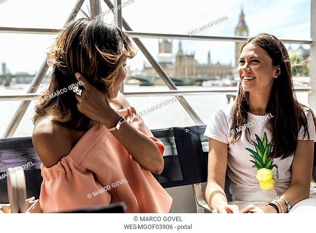 UK, London, two happy women traveling by boat on the River Thames