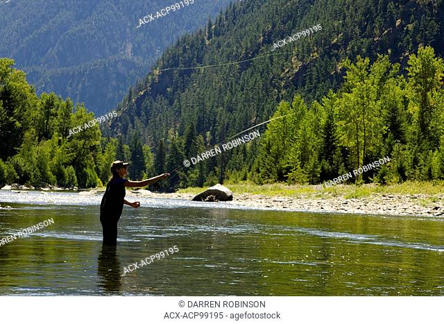 Woman enjoys fly fishing the Similkameen River, near Princeton in the Similkameen region of British Columbia, Canada. MR022