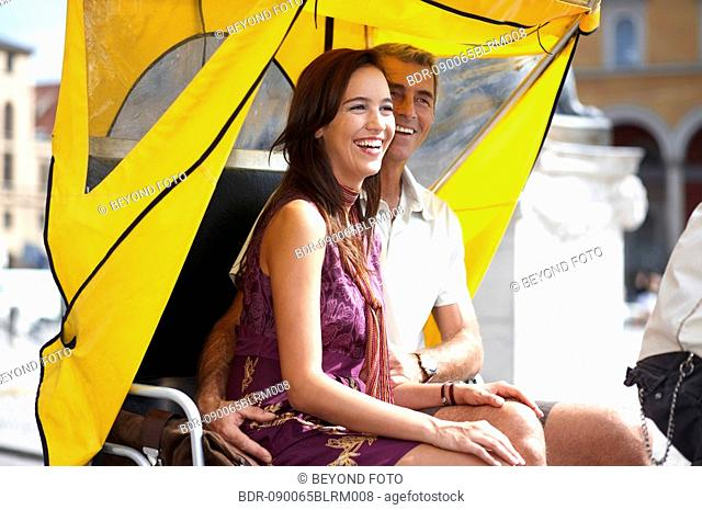 couple driving through city in trishaw