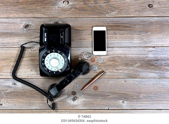 Overhead view of antique phone with modern smartphone on rustic wood