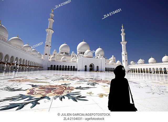 Woman wearing an abaya in the mosque courtyard. United Arab Emirates, UAE, Abu Dhabi, Sheikh Zayed Grand Mosque