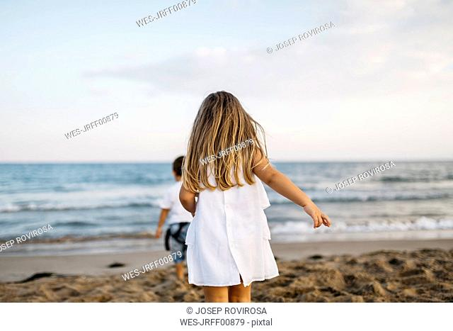 Bck view of little girl playing on the beach with her firend