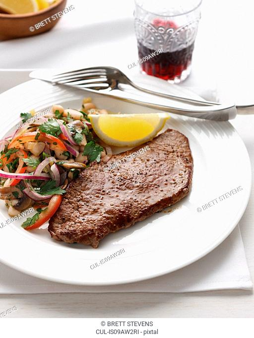 Plate of minute steak with red onion, white beans, tomatoes, parsley and lemon slice