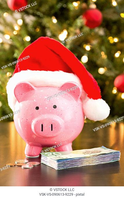 Piggy bank wearing Santa Claus hat placed on table with currency