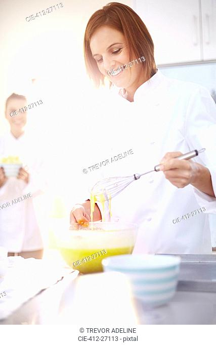 Smiling chef baking in kitchen