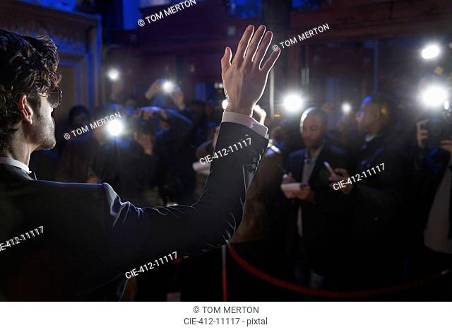 Rear view of male celebrity waving to paparazzi at red carpet event