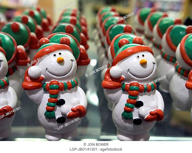 England, Oxfordshire, Oxford. Edible snowman cake and tree decorations in a shop window at Oxford covered market