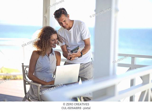 Couple looking at digital tablet and laptop on beach house balcony