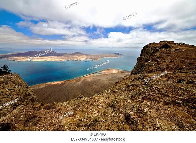 harbor rock stone sky cloud beach water coastline and summer in lanzarote spain graciosa miramar del rio