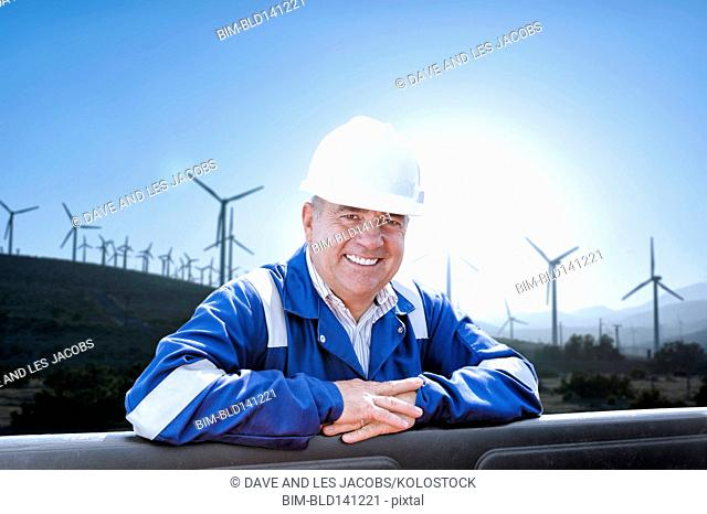 Caucasian technician smiling near field of wind turbines
