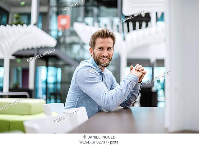 Portrait of smiling businessman sitting at table