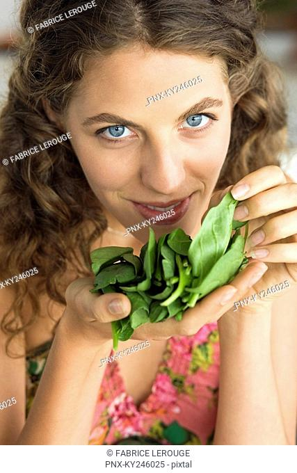 Woman smelling spinach leaves in the kitchen