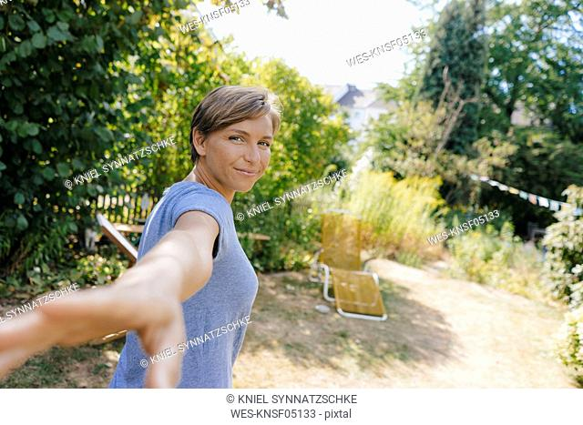 Portrait of smiling woman in garden reaching out