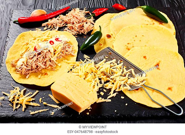 close-up of homemade corn tortillas with shredded meat, sauce, grated cheese and pieces of chili on black stone board, view from above