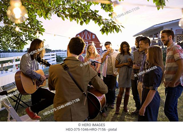 Group of friends listening to band playing during outdoor party