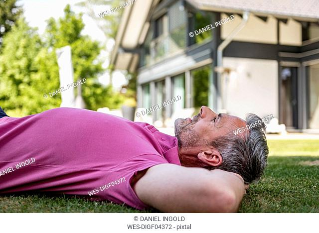 Mature man lying in garden of his home